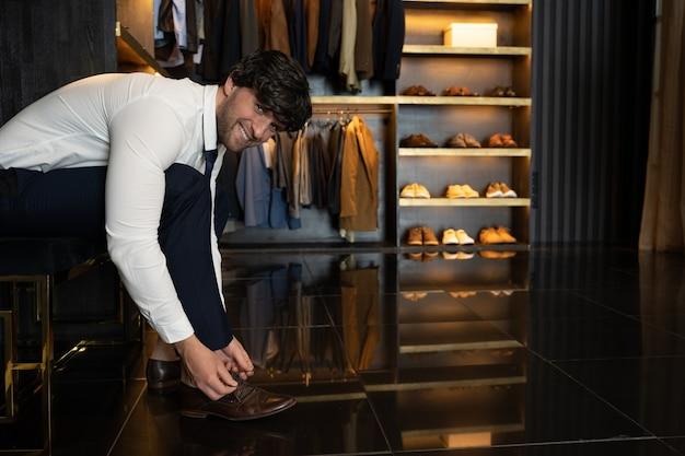 Бизнесмен надевает коричневые туфли в гримерной