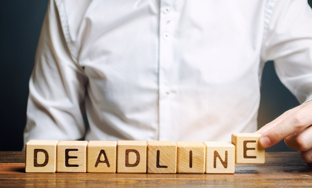 Businessman puts wooden block the word deadline