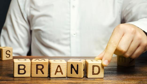 ビジネスマンは、ブランドという言葉で木製のブロックを置きます。ビジネス、マーケティング、広告。