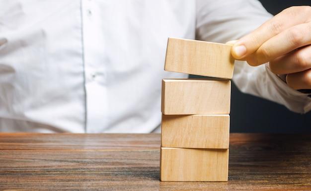 ビジネスマンは木製のブロックを置きます。