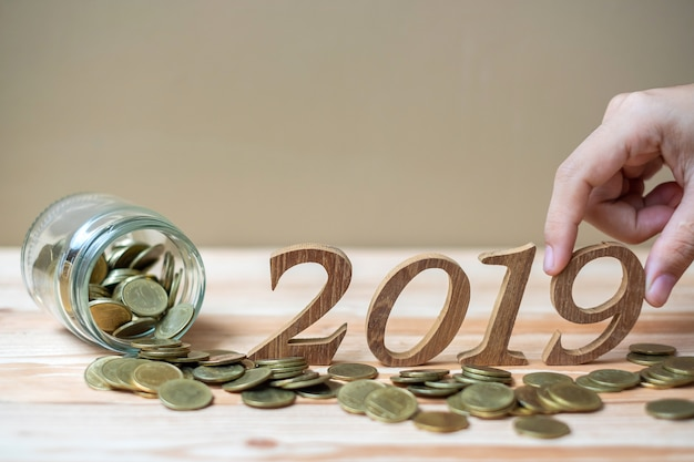 "Businessman putting  ""2019"" wooden number with gold coins stack"