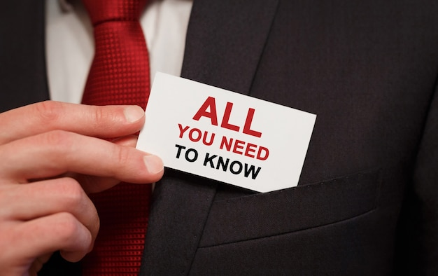 Бизнесмен кладет карту с текстом все, что вам нужно знать в кармане