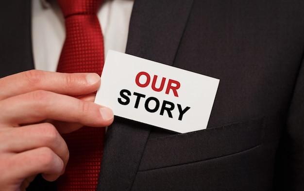 ポケットにテキスト私たちの物語のカードを置くビジネスマン
