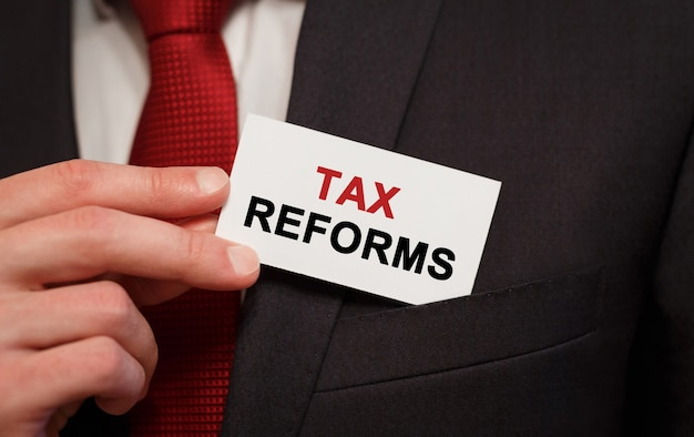 Бизнесмен кладет карту с текстом налоговых реформ в карман