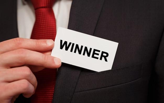 Бизнесмен кладет карту с текстом победитель в карман