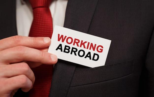 ポケットに海外で働くテキストのカードを置くビジネスマン