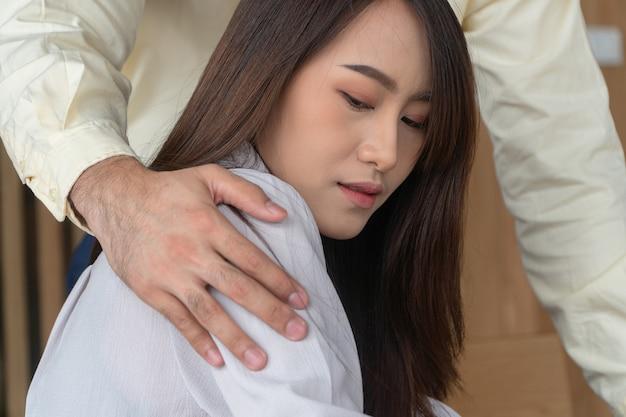 職場の女性従業員の肩に手を置くビジネスマン
