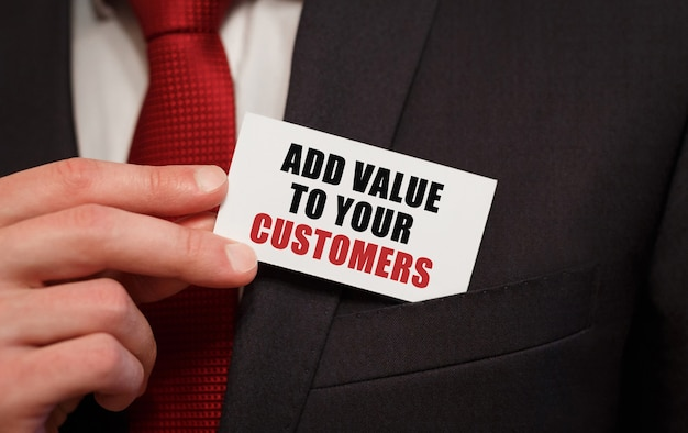 Businessman putting a card with text add value to your customers in the pocket