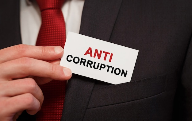 Businessman putting a card with text anti corruption in the pocket