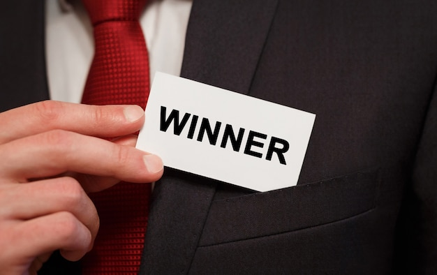 Businessman putting a card with text winner in the pocket