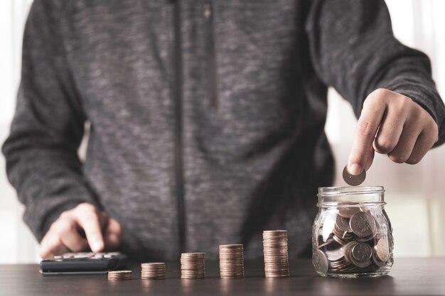 電卓を使用して瓶と片手を節約するためにコインを置くビジネスマン