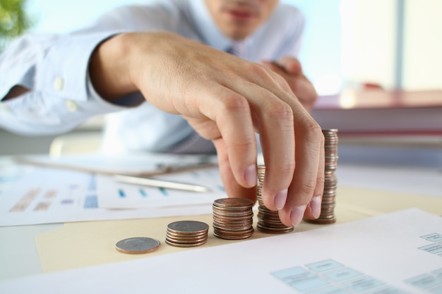 Businessman putting coins in pile on table