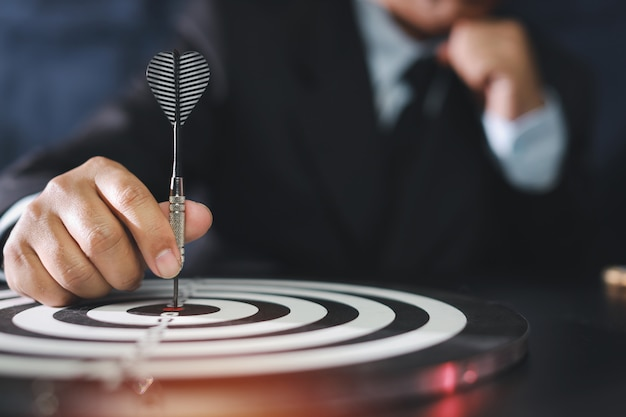 Businessman putting dart in the center of the target