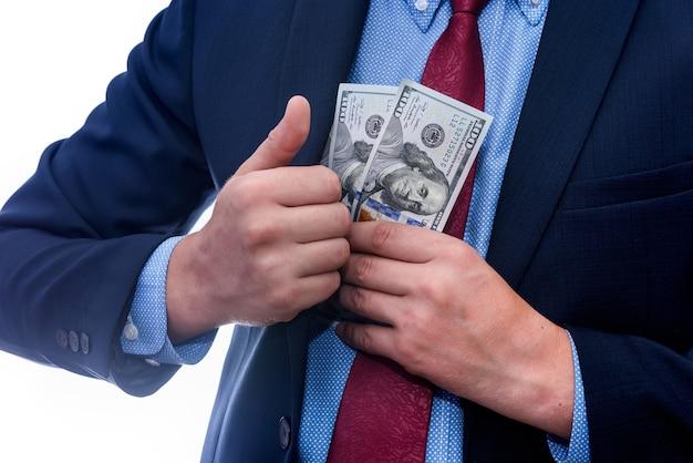 Бизнесмен кладет долларовые банкноты в карман пиджака