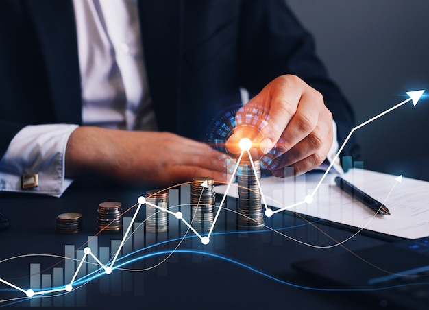Businessman putting money coin stack with growing business digital graph financial investment