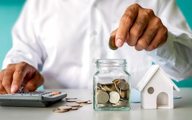 Бизнесмен, вкладывая деньги в сберегательную бутылку и модель дома, финансовую концепцию. ипотечное жилищное кредитование и жилищная недвижимость