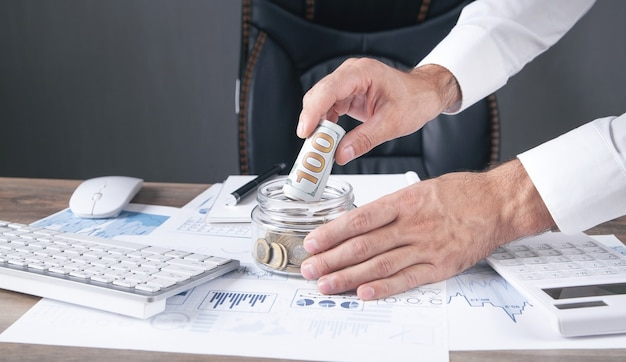 ガラスの銀行にお金を入れているビジネスマン。お金を節約