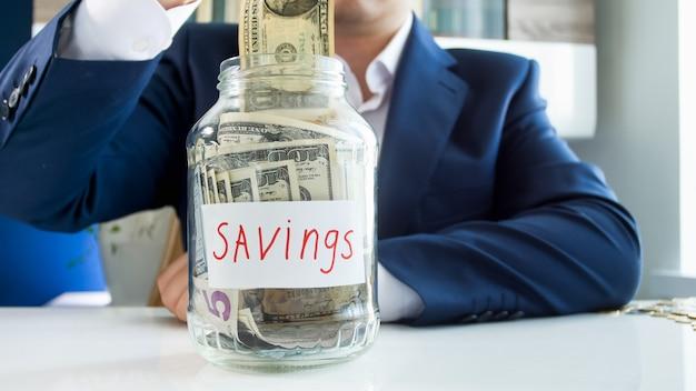 저축을 위해 유리 항아리에 돈을 걸고하는 사업가. 금융 투자, 경제 성장 및 은행 저축의 개념.