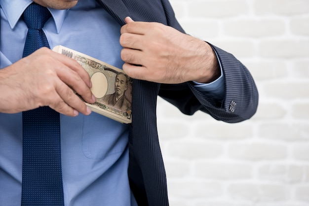 Businessman putting money, japanese yen banknotes, into his suit pocket
