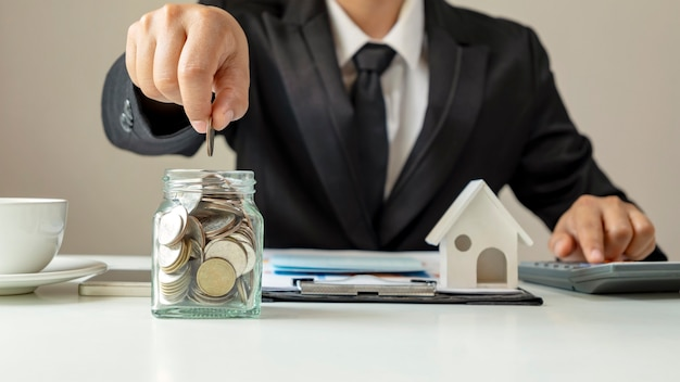 Businessman putting money in a savings bottle and house model, financial concept. home mortgage and residential real estate loans