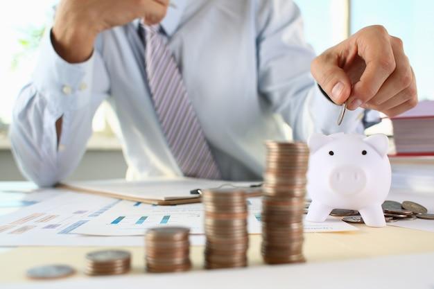 Businessman putting pin money in piggy bank