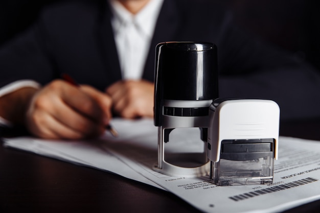 Businessman putting stamp on documents in the office. business concept