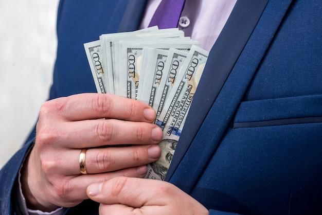 Businessman putting us money into his suit pocket