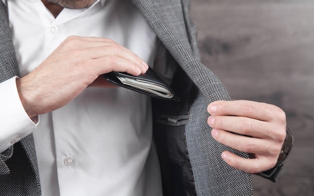 Бизнесмен кладет бумажник с банкнотами в карман костюма.