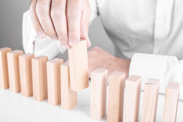 Бизнесмен, ставя деревянные блоки в ряд