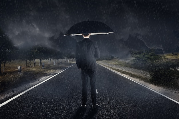 Businessman in rain with umbrella standing