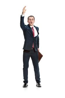白いスタジオの背景に手を上げるビジネスマン。スーツを着た真面目な青年。ビジネス、キャリアの概念。