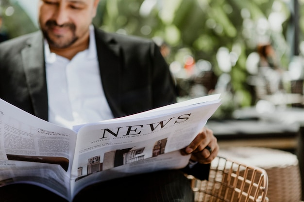 カフェで新聞を読んでいるビジネスマン