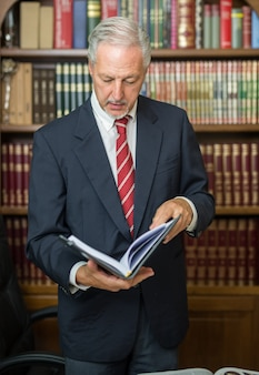 Businessman reading a book in a library