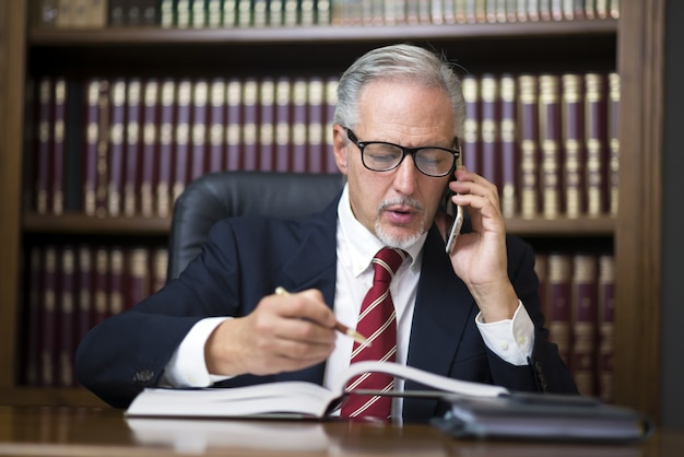 Businessman reading a book while talking on his mobile phone