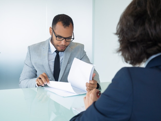 Businessman reading contract during meeting