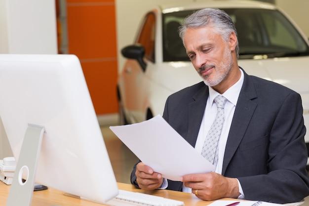 Бизнесмен, чтение документа на рабочий стол