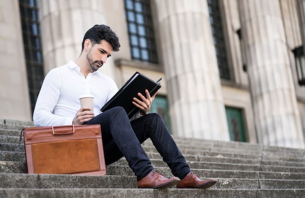 ビジネスマンは、屋外の階段に座ってファイルを読んだり、コーヒーを飲みます。ビジネスコンセプト。