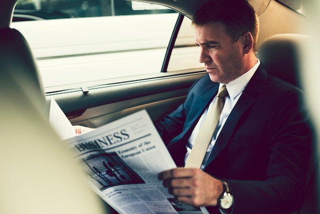 Businessman reading the news in the car
