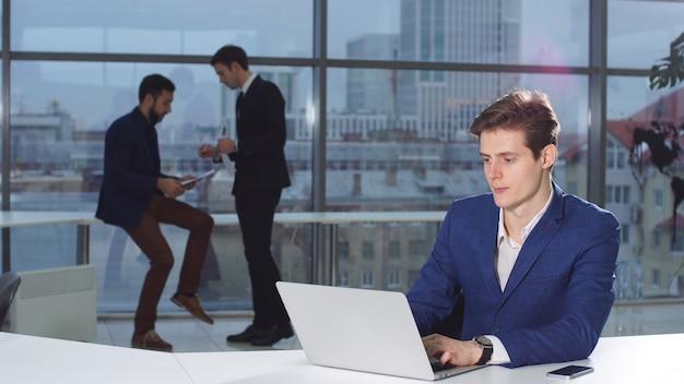 Новости чтения бизнесмена на портативном компьютере на coworking космосе.