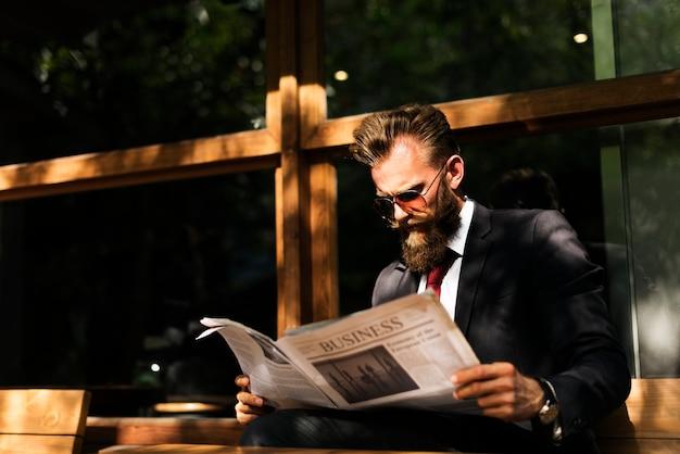 Businessman reading newspaper at coffee shop