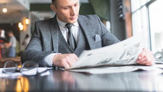 Businessman reading newspaper in caf�