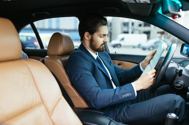 그의 조수를 기다리는 동안 그의 차에서 신문을 읽는 사업가.
