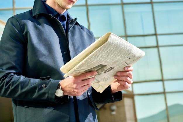 Бизнесмен читает газету на открытом воздухе