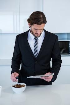 Бизнесмен читает газету во время завтрака на кухне