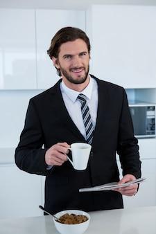 Газета чтения бизнесмена пока имеющ кофе в кухне