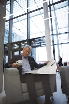 Businessman reading newspaper while having coffee