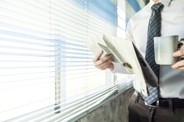Businessman reading newspaper while standing at a window in an office.
