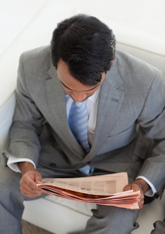 Businessman reading a newspaper while waiting for a job interview