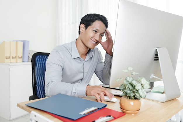 Businessman reading report on computer
