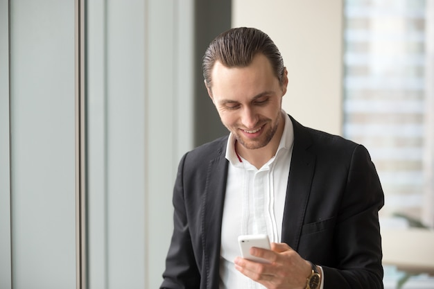 Businessman reading and sending messages on phone